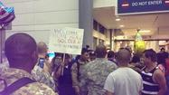 Friends and family members on Sunday await the arrival of members of the Florida Army National Guard's 856 Quartermaster Support Company at Fort Lauderdale's airport.