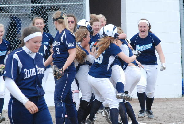 Members of the Petoskey High School softball team celebrate moments following Jenna Proctor's three-run triple in the bottom of the seventh inning to lift them to a 4-3 win over Sault Ste. Marie in a Division II district semifinal at Cheboygan High School. The Northmen then fell to Escanaba, 6-0, in the district final.