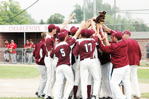Members of the Charlevoix High School varsity baseball hoist the Division III district championship trophy Saturday after they defeated East Jordan, 12-6, in the title game.
