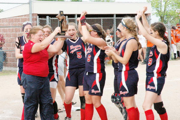 Boyne City coach Sandy Clausen (left) presents her team with the Division III district championship trophy after the Ramblers defeated Harbor Springs, 4-3, in the championship game Saturday at Charlevoix High School.