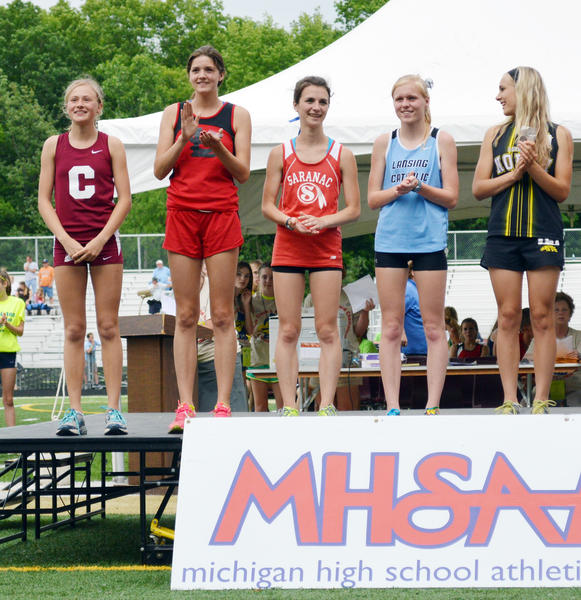 Charlevoix sophomore Amber Way (left) smiles from the podium after winning the Michigan High School Athletic Association Division III girls 3200-meter run Saturday at Comstock Park. Way won the race in a new MHSAA Division III girls record time of 10 minutes, 48.48 seconds, beating the previous record of 10:57.16 set in 2004 by Wyoming Kelloggsvilles Nicole Bush. Raquel Serna (second from left) of St. Louis was second in 10:59.66.