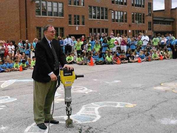 Oak Park D97 Superintendent Al Roberts poses with a jackhammer in front of Irving school to celebrate construction of the new playground.