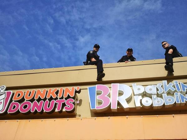 "Glenview patrolmen Dan Domke, Mark Ciesla and Joe Curtis camp out on the Dunkin' Donuts roof as part of the ""Cop on a Rooftop"" fundraising campaign."