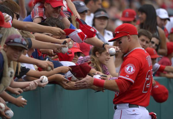 Angels outfielder Mike Trout signs autographs prior to Sunday's game against the Houston Astros.