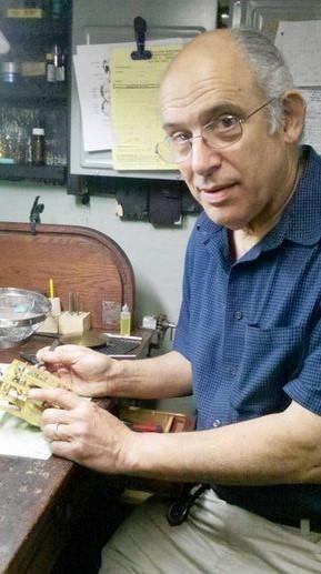 Jim Denno fixing a German wall clock that is more than 100 years old at his shop located inside his home in Palatine.