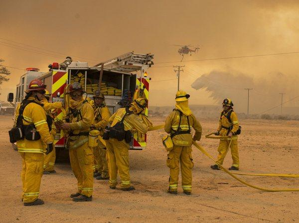 Firefighters prepare to defend a structure while battling the Powerhouse fire near Lancaster.