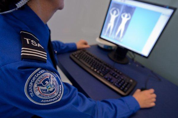 A Transportation Security Administration employee looks at an image from a full-body scanner during a demonstration for members of the media at Logan Airport in Boston.