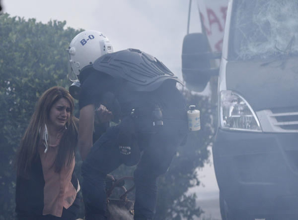 "A police officer helps a woman during an anti-government protest in Istanbul June 3. Turkish Prime Minister Tayyip Erdogan accused anti-government protesters on Monday of walking ""arm-in-arm with terrorism."""