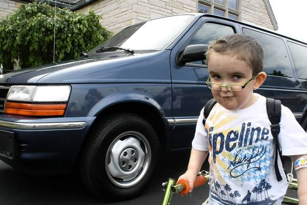 Joseph Donachricha, 6, stands in front of the 1992 Dodge Caravan donated to his mother by a Des Plaines church.