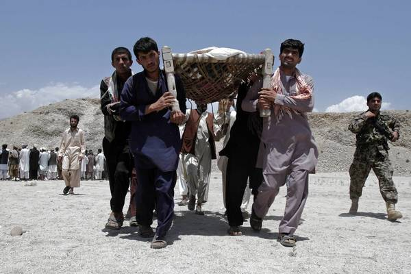 Afghan men carry the bodies of seven civilians killed by a roadside bomb in Laghman province. The family of seven had driven to the mountains to gather firewood, the provincial government said.