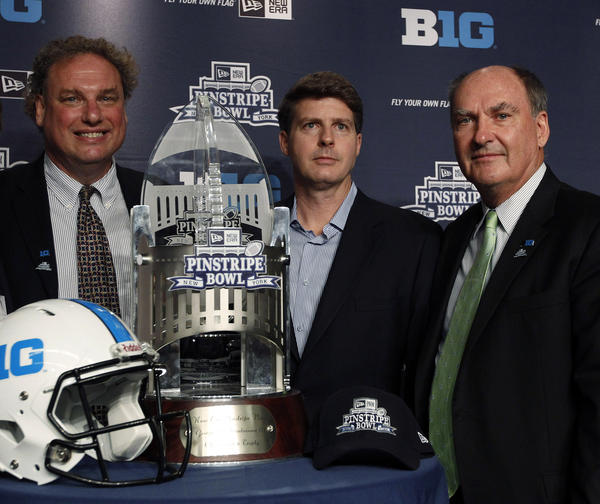 Randy Levine, President of the Yankees, Hal Steinbrenner, Managing General Partner of the Yankees, and Jim Delany, Commissioner of the Big Ten Conference, pose with the New Era Pinstripe Bowl trophy during a press conference to announce the New Era Pinstripe Bowl's eight-year partnership with the Big Ten Conference at Yankees Stadium.