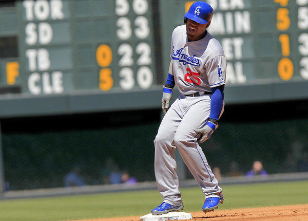 Dodgers' Carl Crawford (25) comes up lame after hitting a double against the Colorado Rockies.