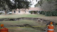 A sinkhole swallowed a sizable portion of an Orange County backyard and a swimming pool Monday night, prompting the homeowner to move out for at least the night.