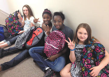 Sixth-graders went shopping and put together Hero Packs at Girls Inc. to be delivered. Sitting, from left, are Amaya Shirley, Faith Osuji, Denae Reynolds and Christine Free.