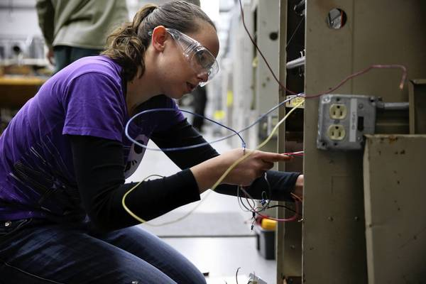 Sarah Cole, 25, rewires a forced air gas furnace in April at Harper College in Palatine. Cole, a Roosevelt University graduate, is pursuing a heating, ventilation and air-conditioning certification at Harper.