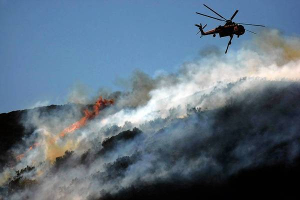 A helicopter drops water on a ridge near Lake Hughes as the Powerhouse fire continues its rampage. The blaze, which started Thursday, has burned more than 32,000 acres and has destroyed at least seven structures.