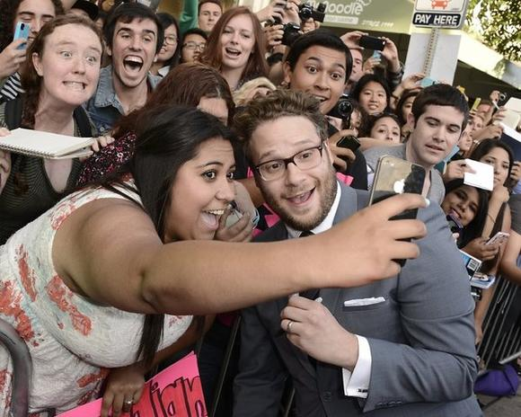 "A fan takes a picture with Seth Rogen at the premiere for ""This Is the End"" in Westwood."
