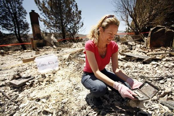 Holly Solberg looks through the debris of her mother's Lake Hughes home on Newview Road that was destroyed by the Powerhouse fire. Holly and her five siblings were raised in the house that her parents, Dorothy and Howard Solberg, moved into 44 years ago.