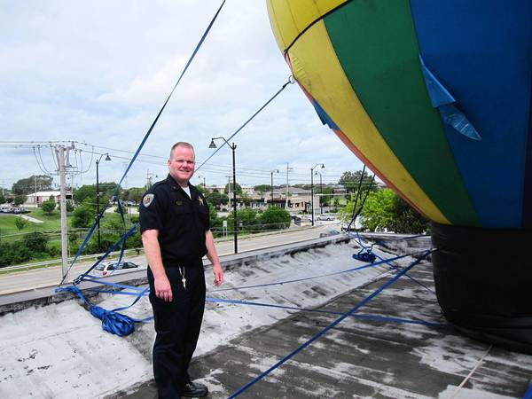 "Tinley Park police Sgt. William Devine participates in a ""Cop on Top"" fundraiser at the Dunkin' Donuts in Tinley Park. Standing atop the doughnut shop's roof, Devine helped raise nearly $5,800 for Special Olympics."