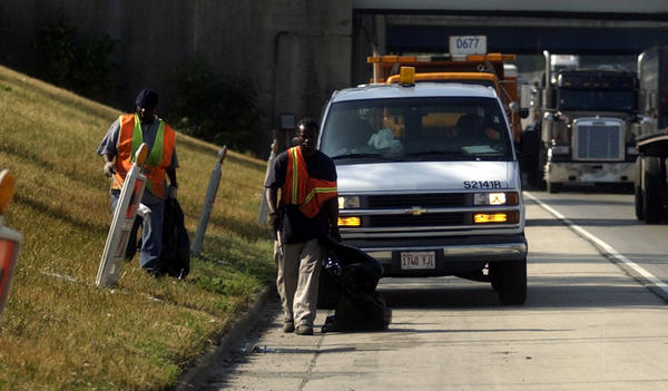 Chicago city workers pick up litter along the Dan Ryan expressway in 2002, while IDOT trucks back them up, offering safety from speeding traffic.