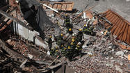 Authorities were searching for at least two people believed to be trapped beneath the rubble of a  collapsed building in downtown Philadelphia after 12 people escaped with minor injuries, officials said Wednesday.