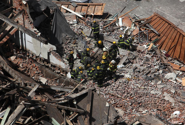 Rescue personnel work at the scene of a collapsed four-story building in downtown Philadelphia on Wednesday. Twelve people were injured and two others are believed trapped beneath the rubble, the fire commissioner said.