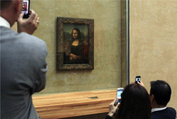 "Visitors take photos of the ""Mona Lisa"" by Leonardo da Vinci at the Musee du Louvre in Paris. The lighting will soon be enhanced."