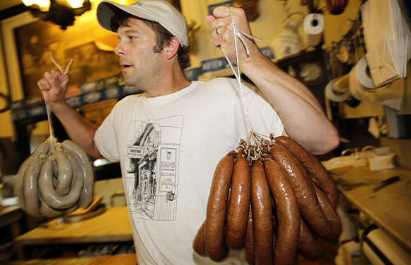 David  Wooley carries liverwurst and German bologna to the meat case at Drier's Meat Market in Three Oaks, Mich.