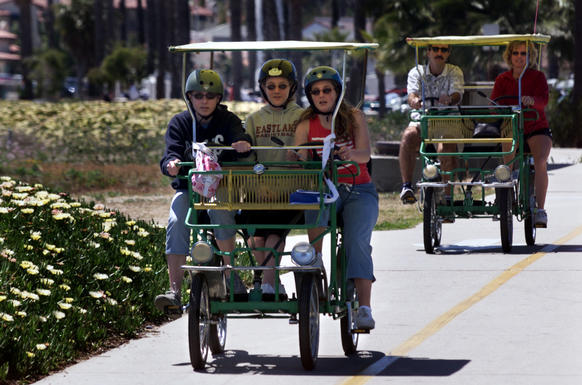 A group in a surrey pedals along a bike path that runs along the beach.