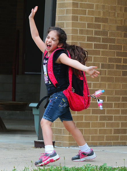 Jayla Calderon shows her excitement as she walks out of Hancock Elementary School on Wednesday. Washington County of Public Schools are on summer break until August.