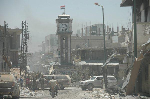 Syrian soldiers patrol damaged areas in the city of Qusair after claiming to have seized control of the city. Some opposition activists say rebel forces remain in part of the strategic city.