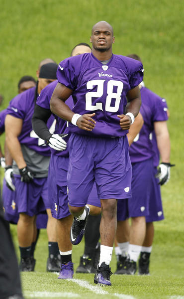Vikings running back Adrian Peterson leads his group through stretching exercises at organized team activities at Winter Park.