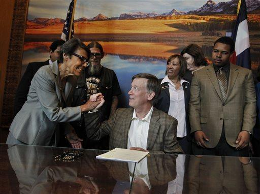 Colorado Gov. John Hickenlooper, center, shakes hands with state Sen. Lucia Guzman after signing a bill she helped sponsor that compensates those wrongly convicted for their time behind bars.