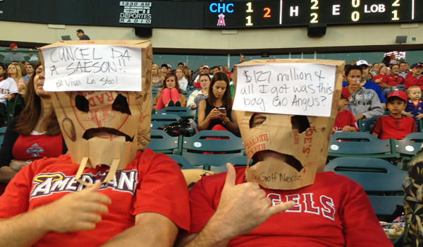 Angels fan Henry Bouldin, right, couldn't bear to watch his team play baseball so he wore paper bag over his head, which stadium security made him remove.
