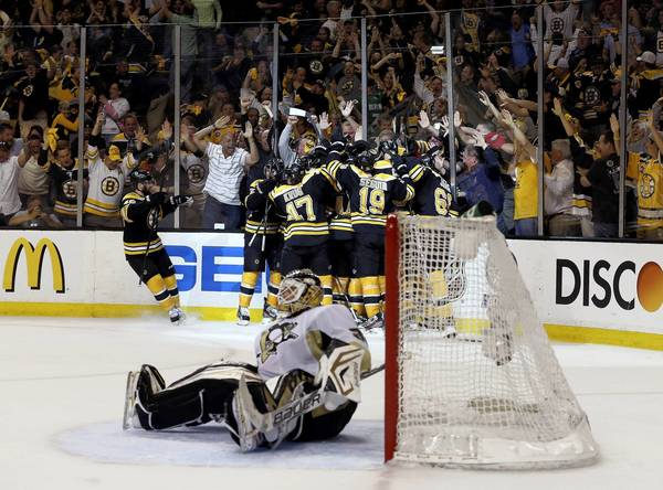 The Boston Bruins celebrate a double overtime victory over the Pittsburgh Penguins on a goal scored by Patrice Bergeron.