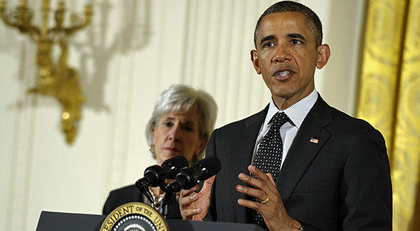 President Barack Obama, standing next to Health and Human Services Secretary Kathleen Sebelius.