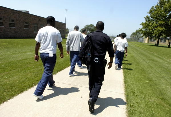 Youths, escorted by a supervisor, walk to a classroom building at the Illinois Youth Center-Joliet in July 2006.