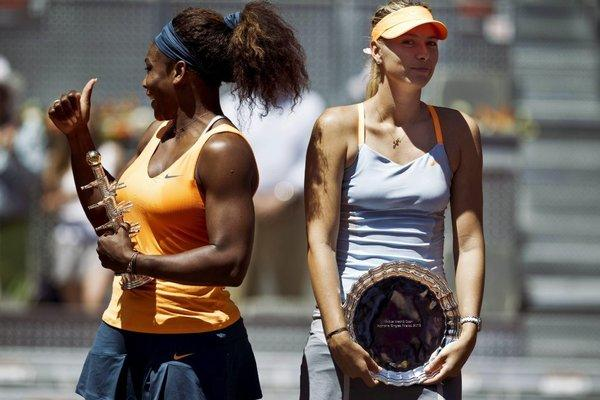 Serena Williams, left, poses with a trophy after beating Russian Maria Sharapova in the Madrid Open Final on May 12.
