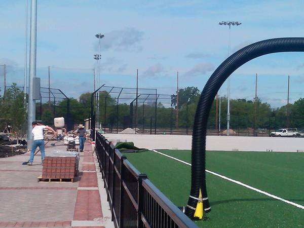 Workers focus their efforts on the walkway beside the Skokie Playfield's new turf fields, set to open on June 17.