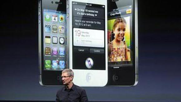 Apple CEO Tim Cook speaks in front of an image of an iPhone 4S at Apple headquarters in Cupertino, Calif. in 2011.
