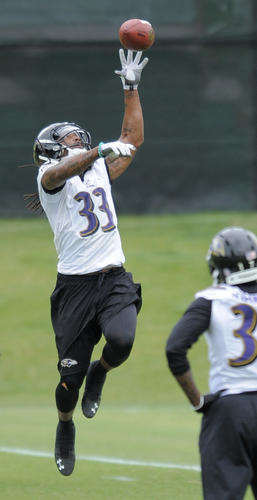 Ravens safety Christian Thompson leaps for the ball during OTAs on Thursday.