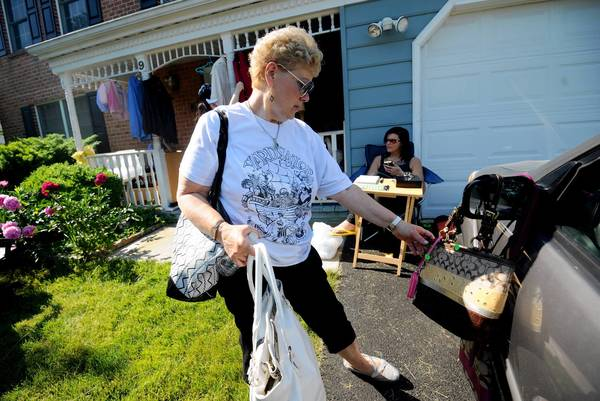 """Yard Sailor"" Ellen Zipper, of Reisterstown, looks at handbags at a yard sale."