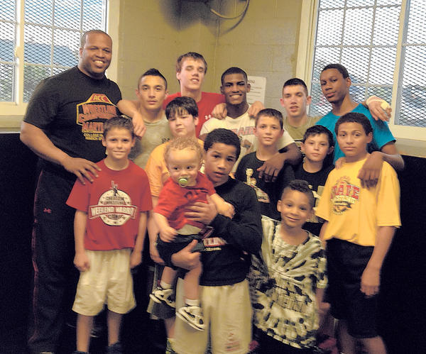 University of Maryland Wrestling Assistant Coach Akil Patterson, top row at left, and U.S. World Team member Ellis Coleman, fourth from left in top row, recently gave local kids some tips at the Police Athletic League facility.
