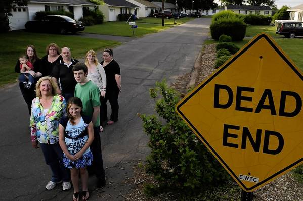 Cheryl Fraser, at front, and her daughter Alia, 9, and son, Bretton Slate, stand with neighbors, from left, Jennifer Valentine and her 1-year-old son Chuck; Jennifer's parents Luce and Joe Malenfant, and their daughters Heather, 16, and Crista, on South Road in East Windsor. Fraser owns a home on Phelps Road, and the Malenfants' home is on South Road. Sixteen property owners in East Windsor who bought houses, but not the land the houses are built on, fear that the 4-acre property could be auctioned off right out from under them because the landowner, Creative Housing Inc., has unpaid taxes on the land.