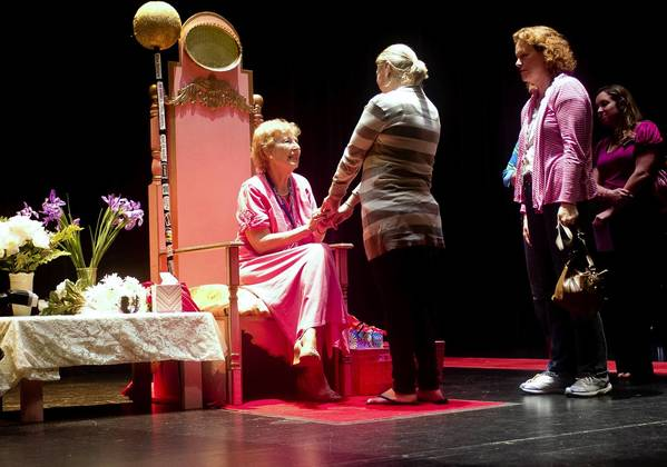Retiring American Heritage School Principal Patricia Butts is greeted by alumni, employees and students while siting on a throne during an event held Thursday.