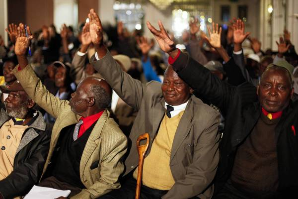 Veterans of the Mau Mau uprising raise their hands in celebration during a news conference in Nairobi, Kenya, at which the British goverment's apology and compensation agreement were announced.