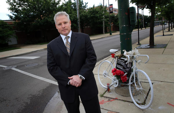 Matt Willens, a Chicago personal injury lawyer, stands near the corner of Oak Street and Wells Street where the ghost bike of Neill Townsend sits.
