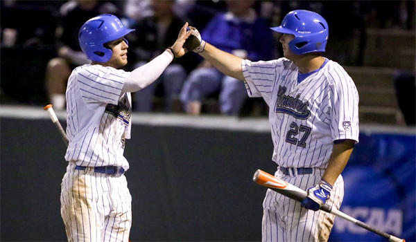 UCLA's Eric Filia and Pat Gallagher celebrate a run during the Bruins' 6-0 victory over San Diego to advance to a super-regional matchup against Cal State Fullerton.