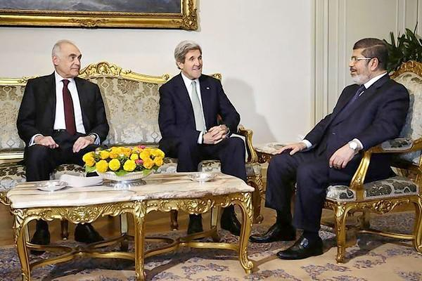 Egyptian Foreign Minister Mohammed Kamel Amr (L), sits with U.S. Secretary of State John Kerry, and Egyptian President Mohamed Mursi (R) during their meeting at the Presidential Palace in Cairo.
