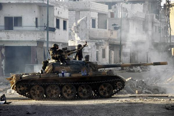 Syrian army troops drive through the ravaged streets of Qusair this week.